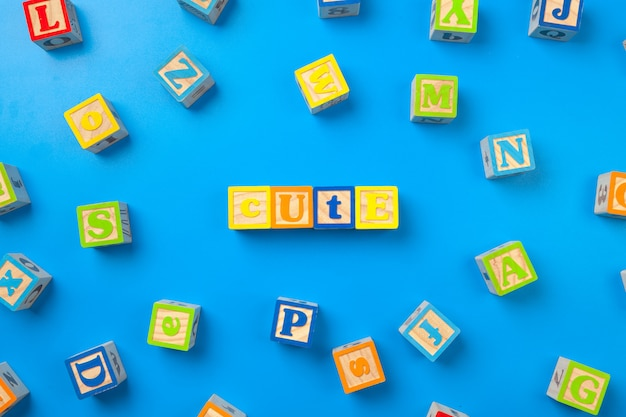 Cute wooden surface colorful alphabet blocks on blue, flat lay, top view