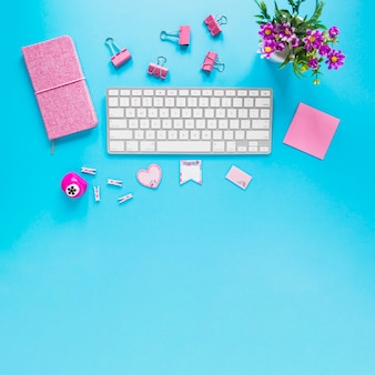 Cute workplace with keyboard and purple stationary