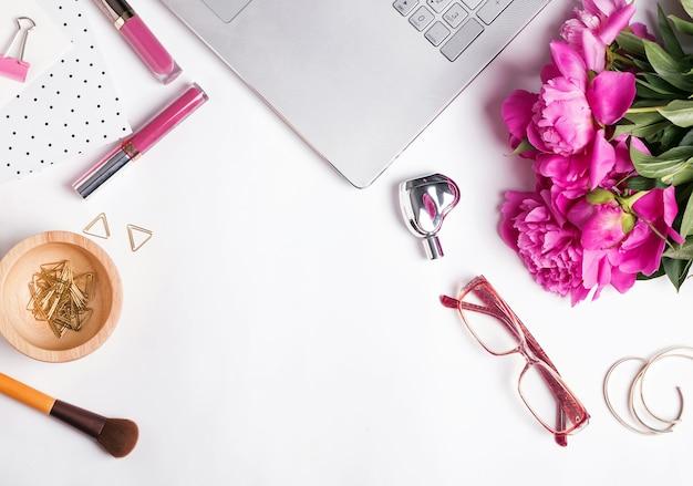 Симпатичное рабочее место с розовыми пионами, ноутбуком и небольшими стильными аксессуарами на фоне белого стола