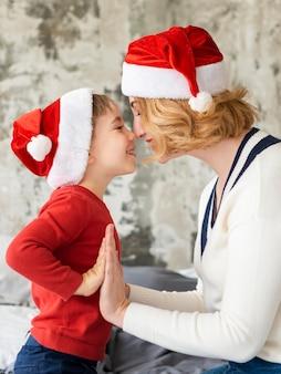 Милая женщина и сын играют на рождество
