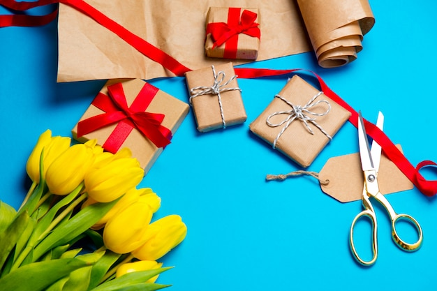 Cute yellow tulips, beautiful gifts and cool things for wrapping on the wonderful blue background