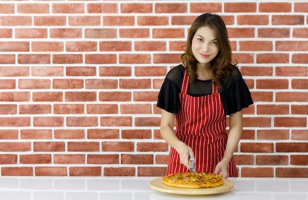 赤い縞模様のエプロンを着たかわいい若いアジア人主婦が、キッチンのレンガの壁の近くに微笑んで立って、おいしい調理済みピザを提供し、木製の皿に割って楽しんでいます