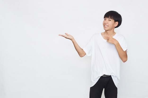 A cute young asian man amazed and smiling at the camera while presenting with a hand and pointing with a finger on white surface