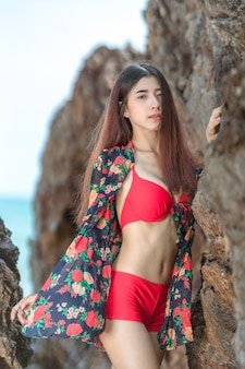 Cute young asian woman in bikini happy on beautiful beach in summer vacation in thailand