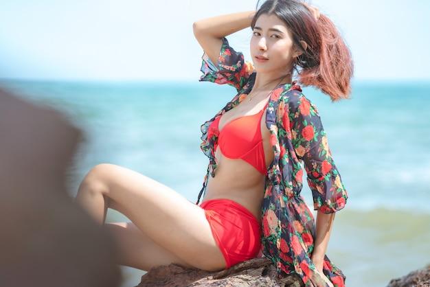 タイの夏休みに美しいビーチで幸せなビキニでかわいい若いアジア女性