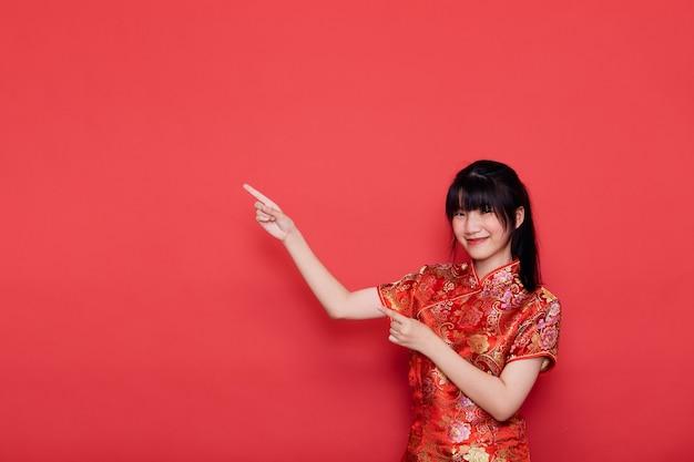 Симпатичная молодая азиатская женщина носит cheongsam, указывая на пустой для концепции китайского нового года на красном