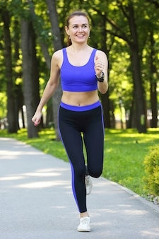 Cute young athletic woman doing sports in nature