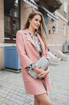 Cute young beautiful stylish woman walking in street in pink coat, holding purse in hands, listening to music