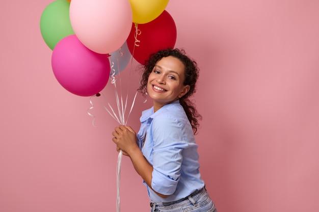 テキストと広告のためのコピースペースとピンクの背景の上に分離された色とりどりの明るい風船をたくさん持っている混血民族のかわいい若い美しい女性