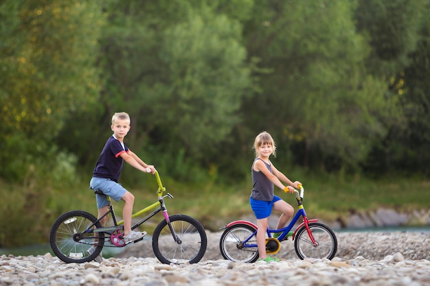 Cute young blond children, boy and girl riding child bicycles on pebbled river bank