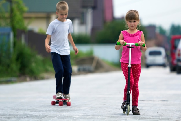 Cute young blond children girl in pink clothing on scooter and handsome boy on skateboard playing on sunny street