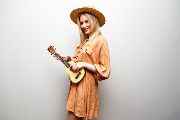 Cute young blonde woman playing ukulele in boho fashionable dress and straw hat