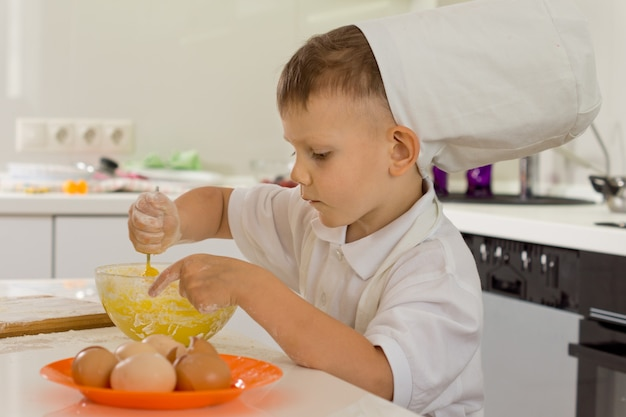 Cute young boy chef whipping the eggs