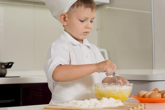 Cute young boy doing the baking