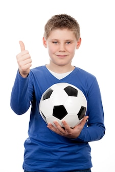 Cute young boy holding a football ball