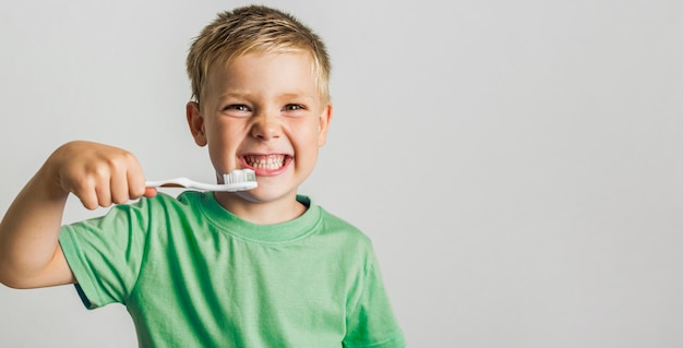 Cute young boy holding toothbrush