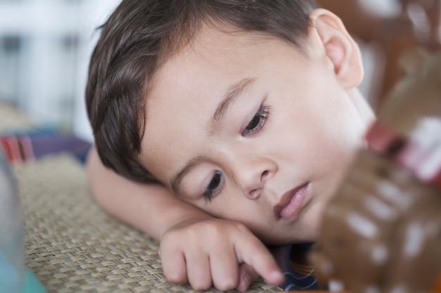 Милый молодой мальчик, кладя голову на стол, выглядит грустным и усталым
