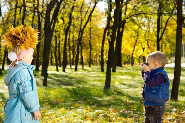 화려한 노란색 가을 컬렉션으로 만든 그의 자매 가을 모자를 촬영하는 귀여운 어린 소년 수집 나뭇잎