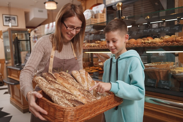 Cute young boy picking fresh bread from the basket in hands of mature female baker