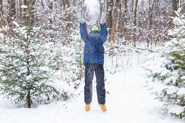 Милый мальчик играет со снегом, веселится, улыбается. подросток в зимнем парке. активный образ жизни, зимние развлечения, зимние игры на свежем воздухе, снежки.