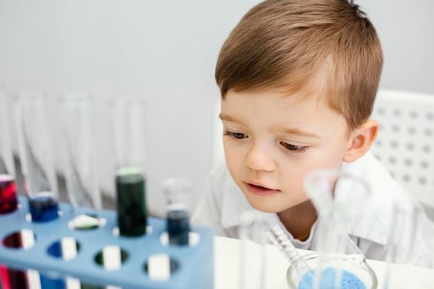 試験管で実験をしているかわいい少年科学者