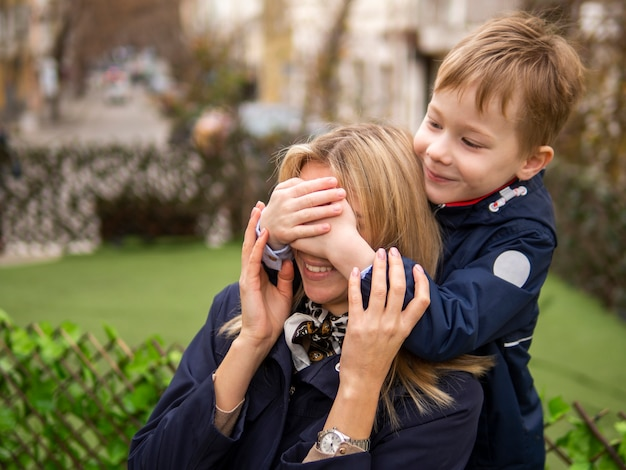 Cute young boy surprising his mother