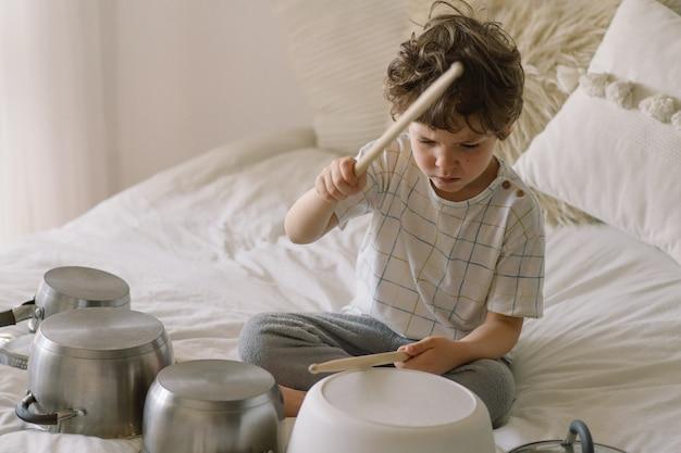 나무 막대기를 사용하여 드럼 세트처럼 설정된 냄비를 두드리는 귀여운 어린 소년