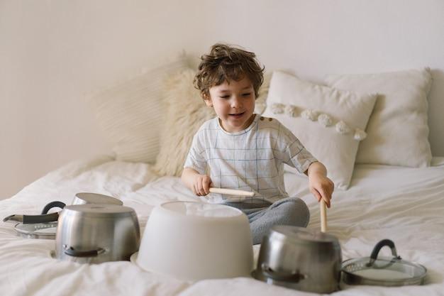 나무 막대기를 사용하여 drumset처럼 설정된 냄비를 쾅하는 귀여운 어린 소년.