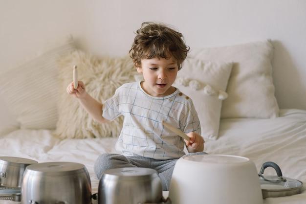 ドラムセットのように設置された鍋を木の棒で叩いてかわいい男の子。