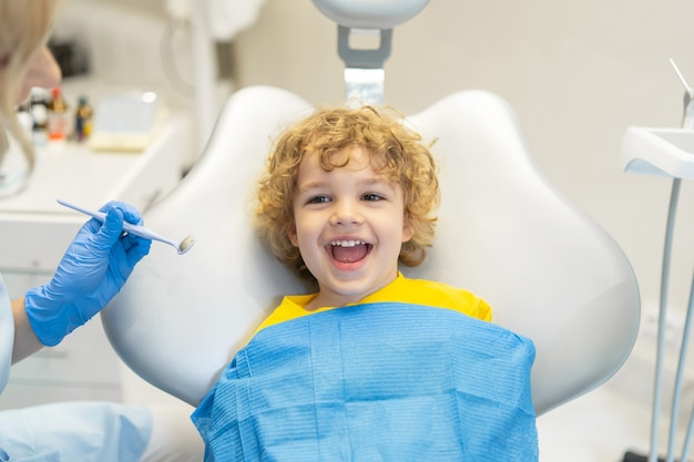 Cute young boy visiting dentist, having his teeth checked by female dentist in dental office.