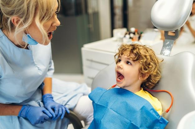 歯科医院の女性歯科医に歯をチェックしてもらう、かわいい少年が歯科医を訪ねる。