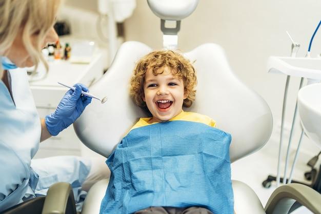 Симпатичный молодой мальчик, посещающий стоматолога, его зубы проверяет стоматолог-женщина в стоматологическом кабинете.
