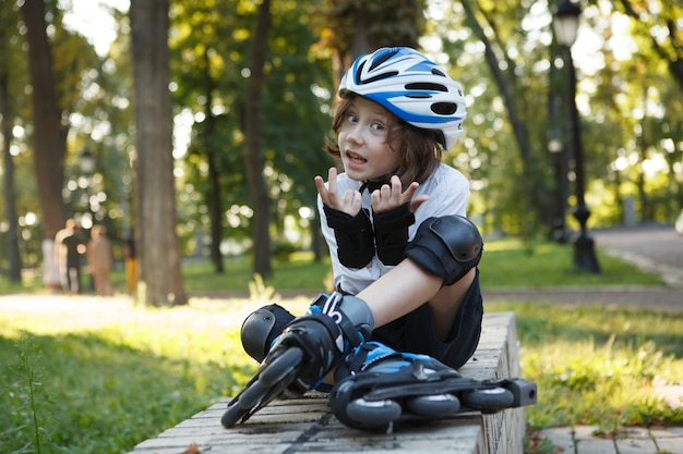 Cute young boy wearing helmet and skates, resting after rollerblading at the park