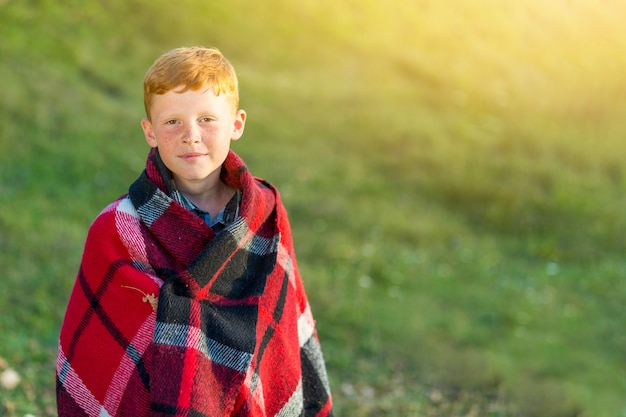 Cute young boy with blanket looking at camera