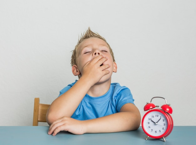 Cute young boy with clock yawning