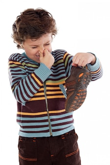 Cute young boy with stinky shoe pitching his nose