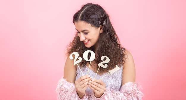 Милая молодая брюнетка с вьющимися волосами и голыми плечами держит в руках деревянный номер на новый год на розовом фоне