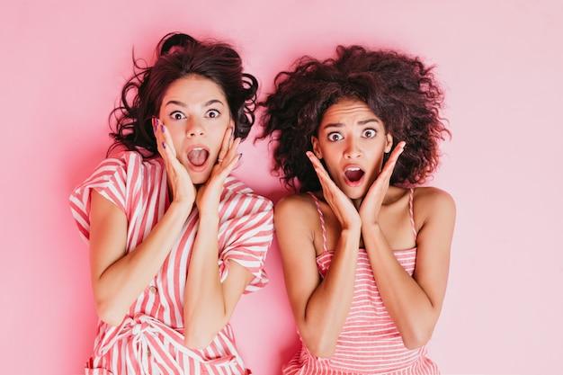 縞模様のピンクのパジャマに身を包んだ、美しい目と柔らかいメイクのかわいい若いブルネットの女の子、非常に怖い表情。