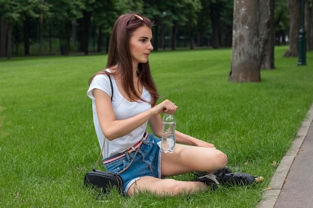 Милая молодая брюнетка сидит на зеленой траве и держит в руках бутылку воды
