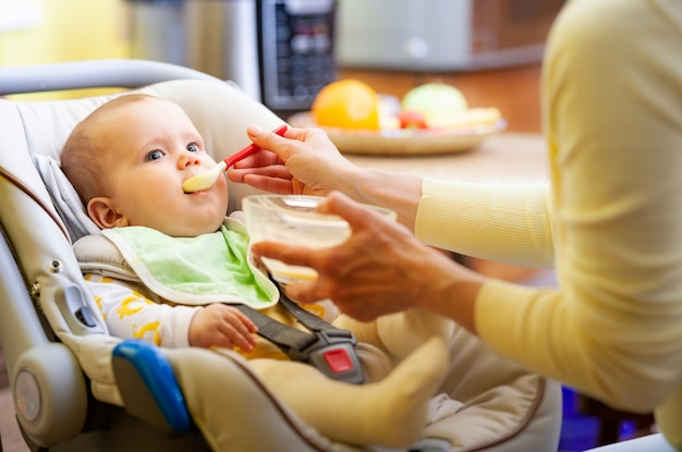 Cute young caring caucasian mother feeds her charming little six-month-old daughter in a cozy living room.