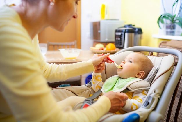かわいい若い思いやりのある白人の母親は、居心地の良いリビングルームで魅力的な小さな生後6か月の娘に食事を与えます。 t
