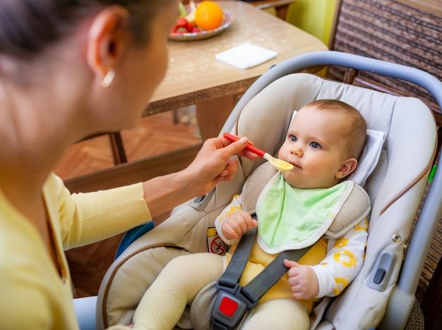 귀여운 젊은 돌보는 백인 어머니는 아늑한 거실에서 매력적인 6 개월 된 딸에게 먹이를줍니다.