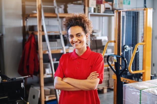 腕を組んで立っているかわいい若い白人女性従業員。印刷店のインテリア。