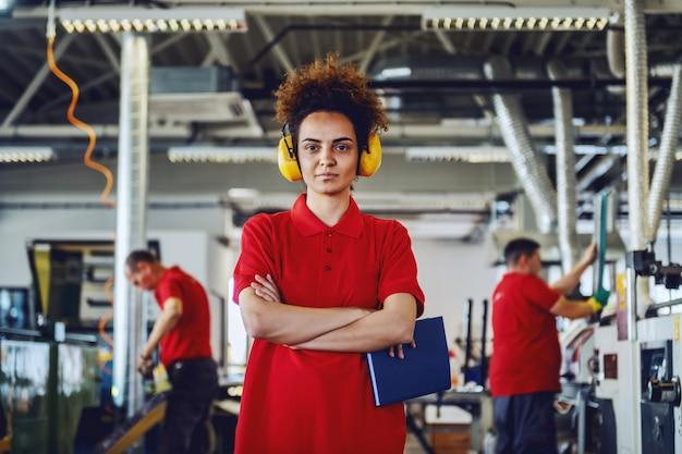 腕を組んで立っているとノートを保持している耳にアンチフォンでかわいい若い白人女性従業員。印刷店のインテリア。