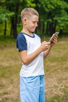 公園でタブレットを使用して作業しているかわいい若い白人の子供