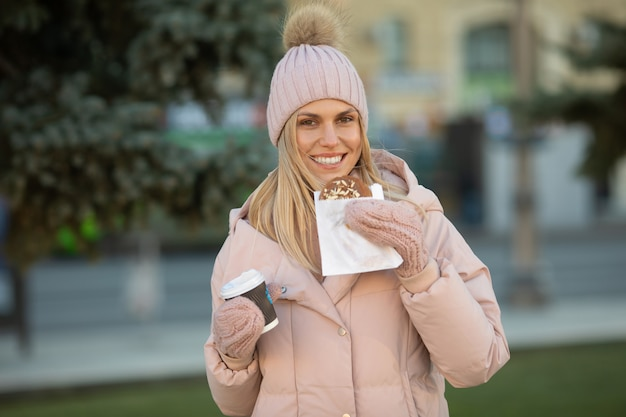 Cute young caucasian teenage woman in beige hat with pompon and pink mittens holding steaming cup of hot tea or coffee, outdoor in sunny winter day.