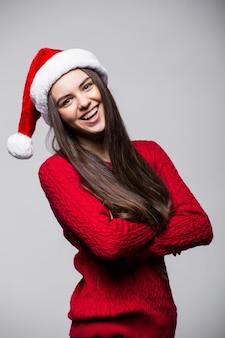 밝은 회색 벽에 웃는 포즈 산타 모자와 장갑을 끼고 귀여운 젊은 백인 여자. 크리스마스와 새 해 개념입니다. 사용 가능한 공간을 복사하십시오.