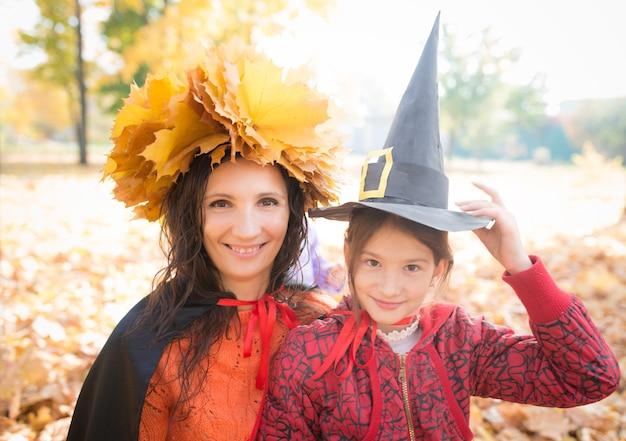 노란색 메이플의 화 환을 가진 귀여운 젊은 쾌활 한 어머니는 그녀의 작은 매력적인 딸과 함께 그녀의 머리에 나뭇잎 가을 공원에서 산책하는 동안 종이 마녀 모자. 할로윈 회의 개념