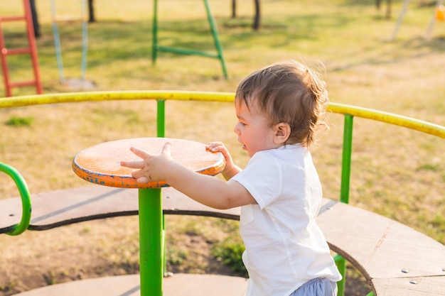 Cute young child boy or kid playing on playground.