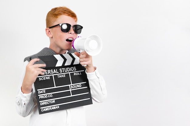 Cute young child holding clapperboard